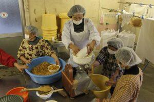 蒸した大豆をつぶす作業をする参加者「JA中海みそ加工場で」
