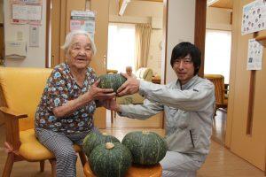 利用者へかぼちゃを手渡す中田支部長(右)(グループホームやたので)