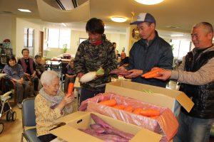 施設利用者に野菜を渡す青壮年部みゆき支部員ら