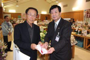 社会福祉協議会へ寄付金を手渡す大上部会長(左)