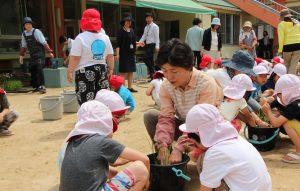 園児らに植え方を教える女性部の中谷さん
